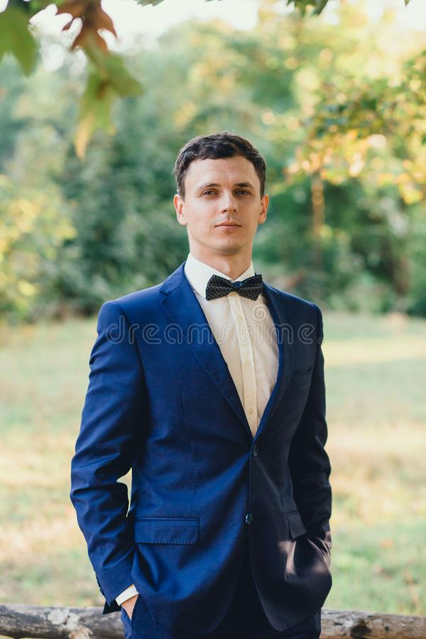 A cute young and attractive groom, dressed in a blue wedding strict fashionable stylish suit and a black bow tie, has royalty free stock photography
