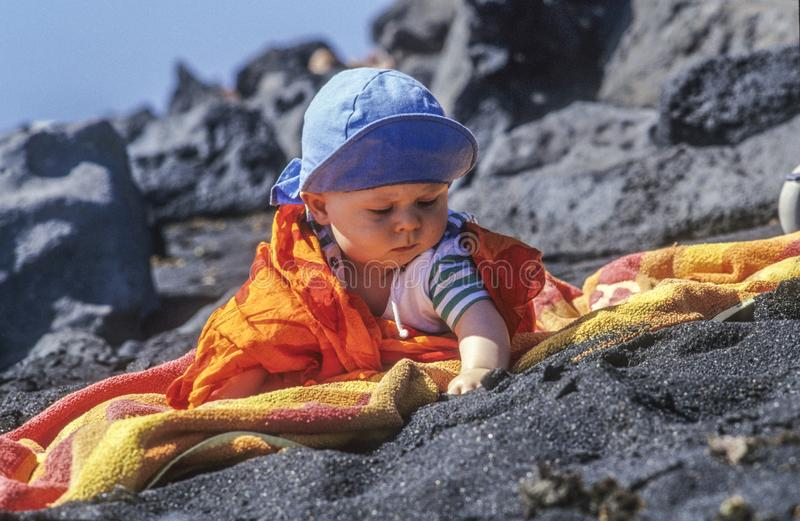 Cute young baby enjoys exploring the black sand at the beach royalty free stock photos