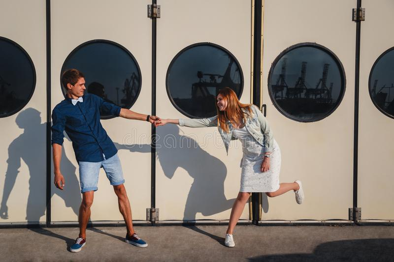 Cute young beautiful couple kidding at port, on the white wall with big portholes background, happy smiling outdoor portrait stock image