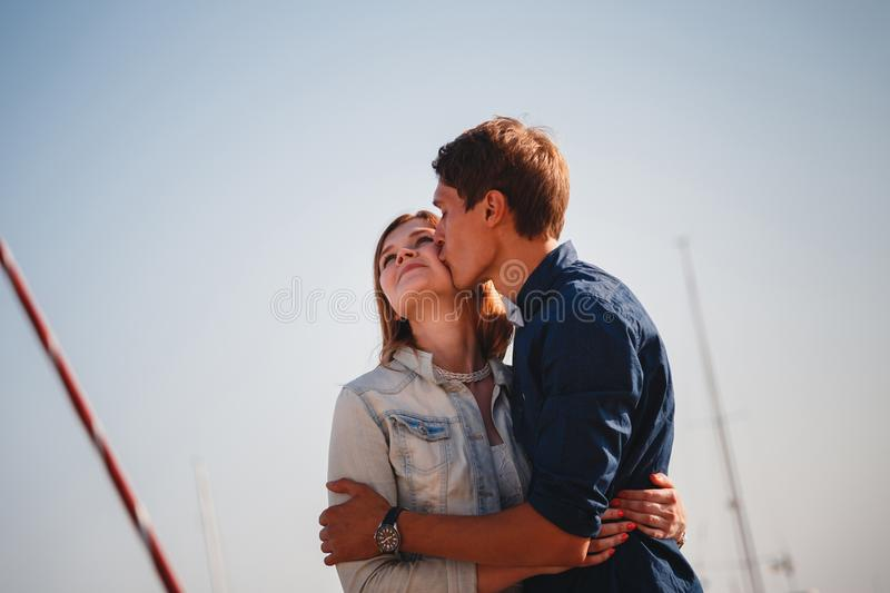 Cute young beautiful couple at pier at port with small yachts, hipster, happy smiling outdoor portrait stock photo