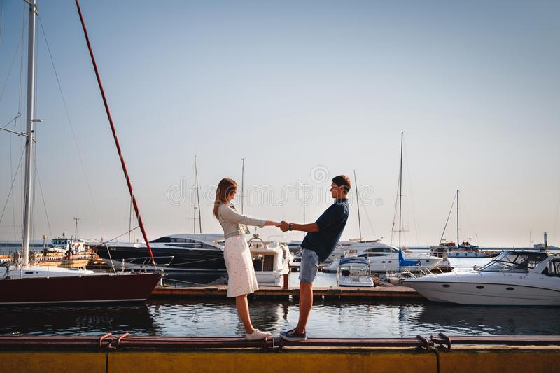 Cute young beautiful couple at pier at port with small yachts, hipster, happy smiling outdoor portrait stock photography