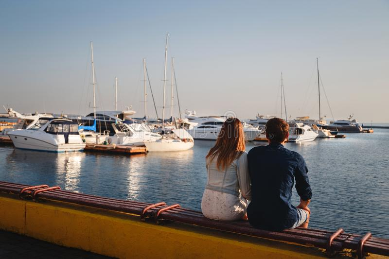 Cute young beautiful couple sitting and hugging together at pier at port, hipsters. Back view.  stock images