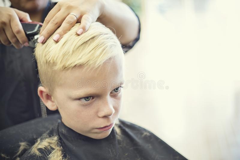 Cute blonde boy getting his hair cut at a beauty salon royalty free stock images