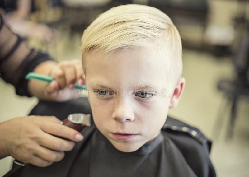 Cute blonde boy getting his hair cut at a beauty salon royalty free stock photos