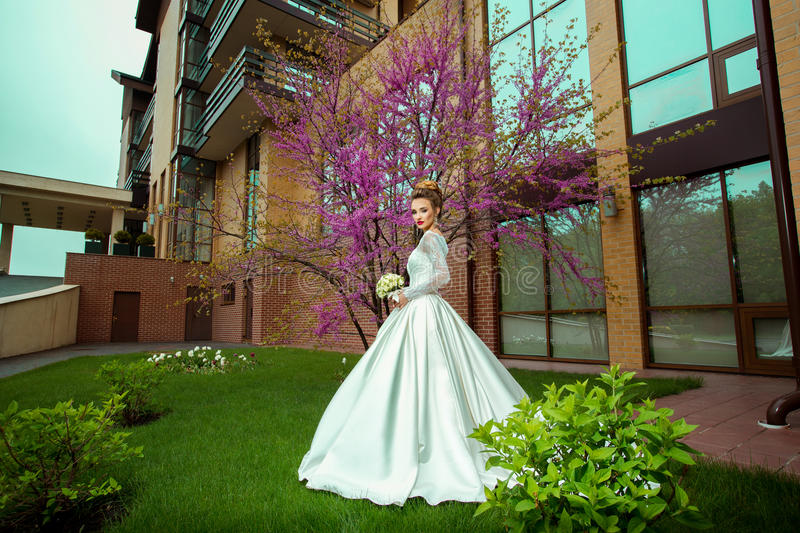 Cute young blonde bride in wedding dress looking at the camera outdoors in fron of sakura tree. Portrait of cute young blonde bride in wedding dress looking at stock image