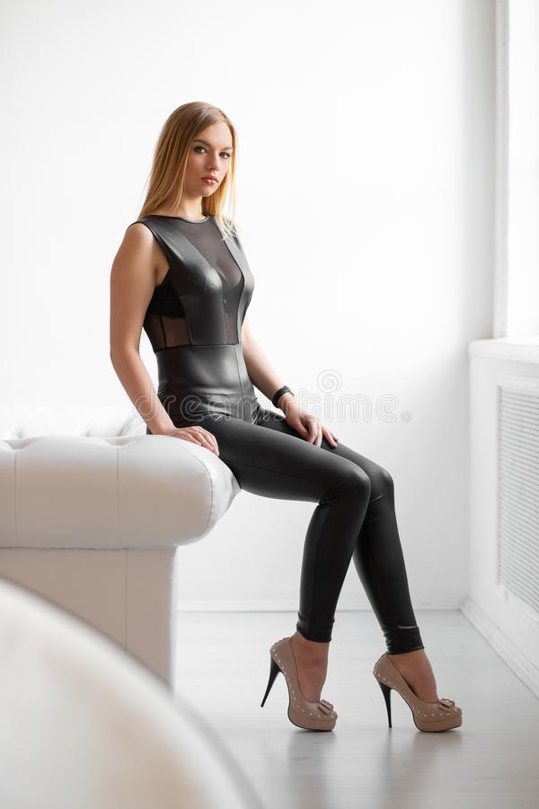 Cute young blonde. Posing in the studio dressed in a black leather suit royalty free stock images