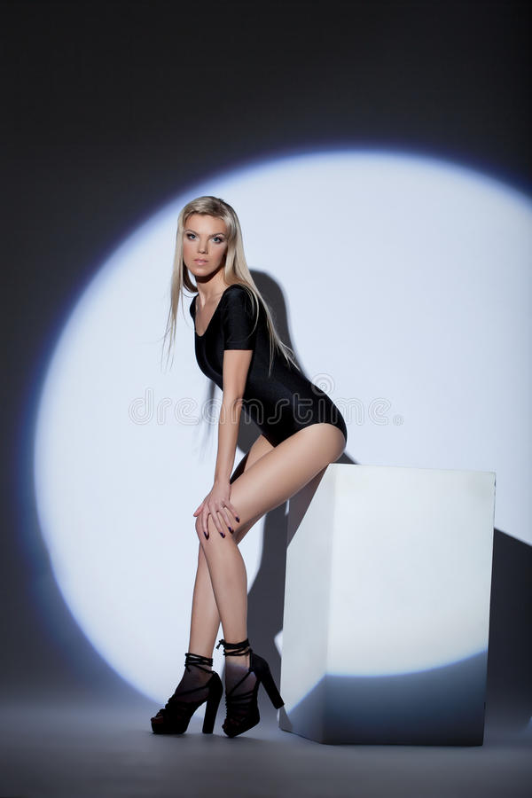 Cute young blonde posing in spotlight royalty free stock photo