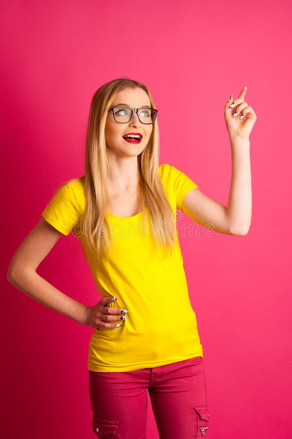 Cute young blonde teenage woman pose over pink background in vibrant yellow t shirt pointing in copy space as advertisement stock photography