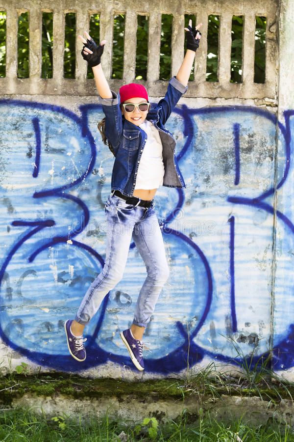 Cute young blonde teenager girl in a baseball cap and jeans shirt jumping against a stone wall background. Hip hop, stock photo