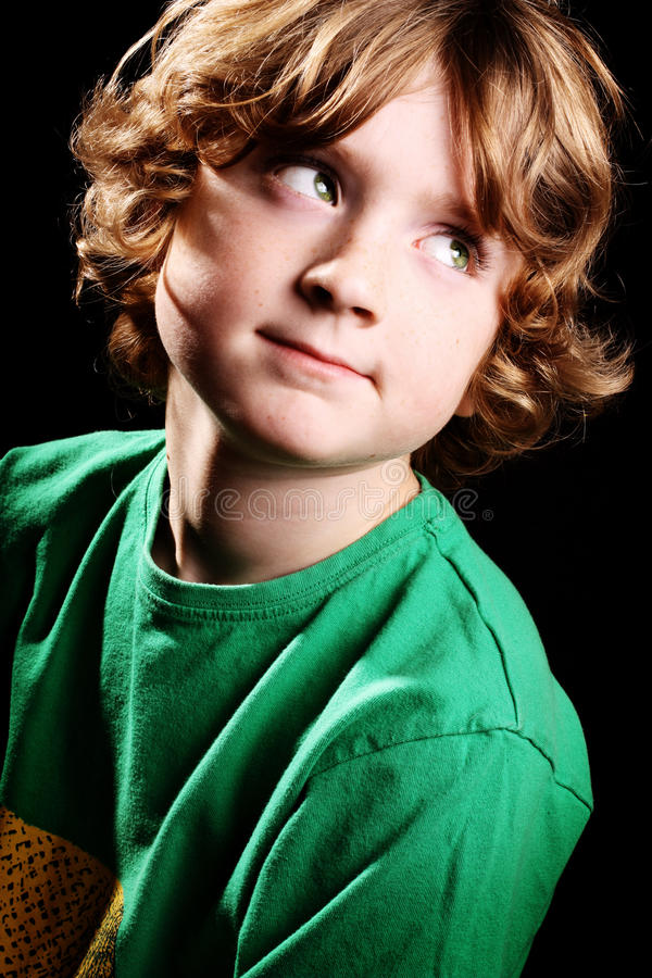 Cute young boy. A cute young boy looking upwards on a black background stock photos