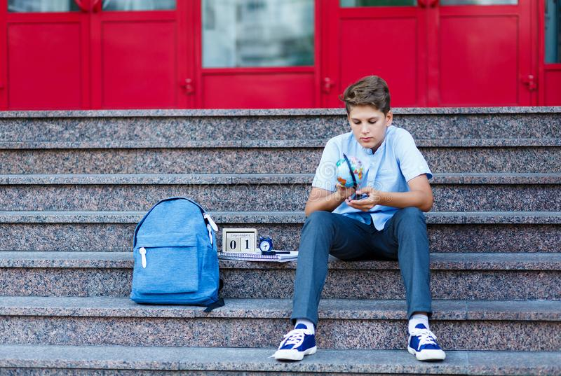 Cute, young boy in blue shirt with backpack holds globe in his hands on the steps in front of his school. Education. Back to school concept stock images