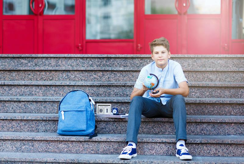 Cute, young boy in blue shirt with backpack put his workbook on his head for fun. He smiles and stands in front of school. Cute, young boy in blue shirt with stock image