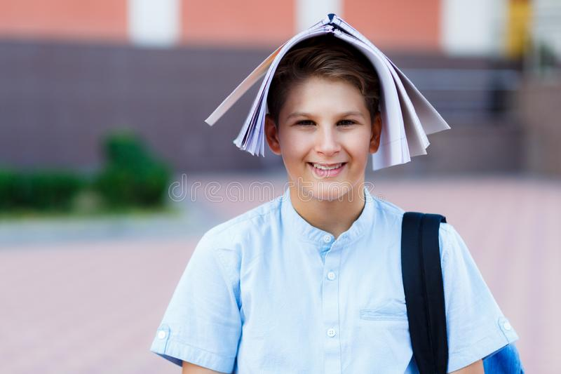 Cute, young boy in blue shirt with backpack put his workbook on his head for fun. He smiles and stands in front of school. Education, Back to school concept stock images