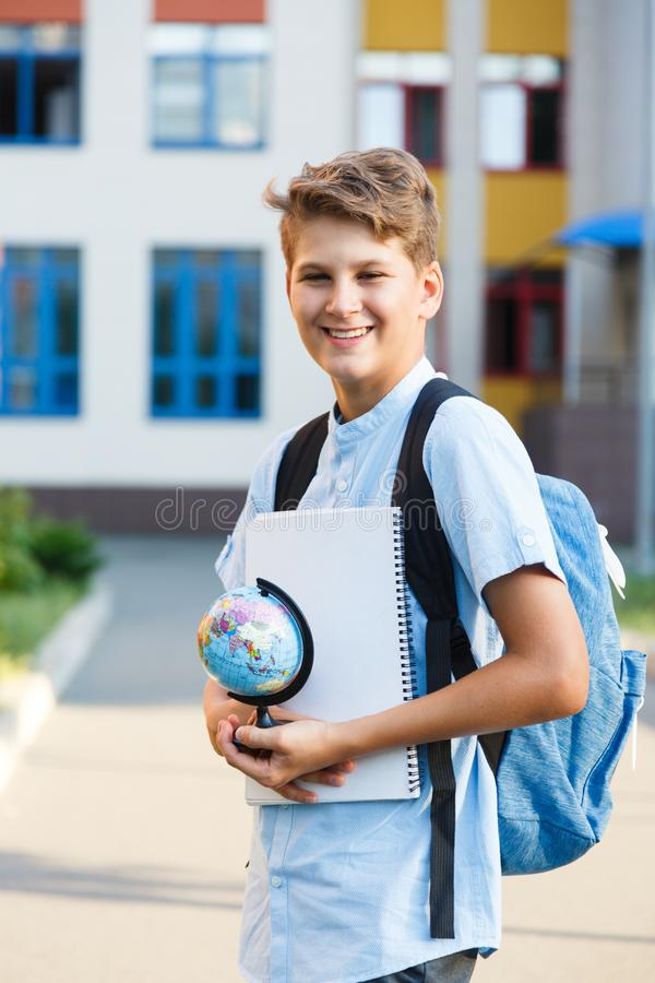 Cute, young boy in blue shirt with backpack stands in front of his school. Education, Back to school. Concept stock photos