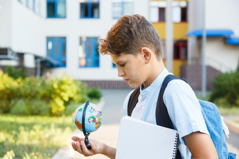 Cute, young boy in blue shirt with backpack stands in front of his school. Education, Back to school. Concept stock images