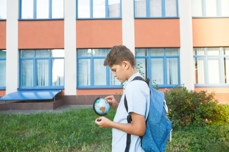 Cute, young boy in blue shirt with backpack stands in front of his school. Education, Back to school. Concept royalty free stock photo