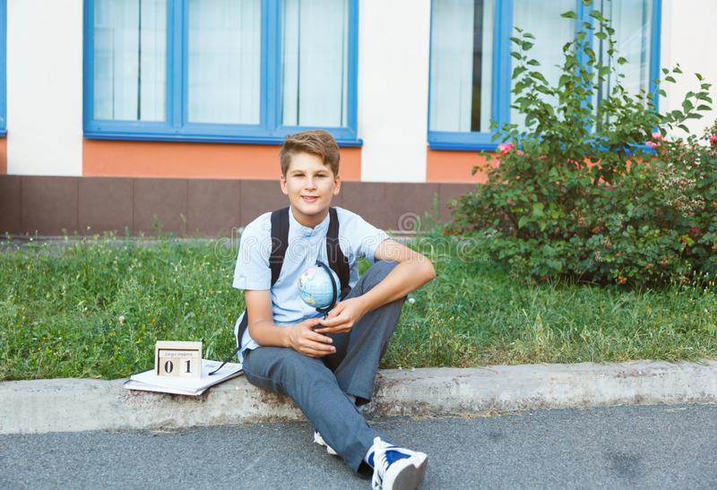 Cute, young boy in blue shirt with backpack stands in front of his school. Education, Back to school. Concept stock photography