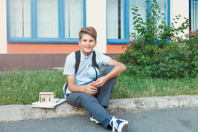 Cute, young boy in blue shirt with backpack stands in front of his school. Education, Back to school. Concept royalty free stock photography