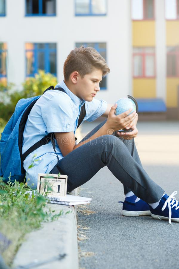 Cute, young boy in blue shirt with backpack stands in front of his school. Education, Back to school. Concept royalty free stock images