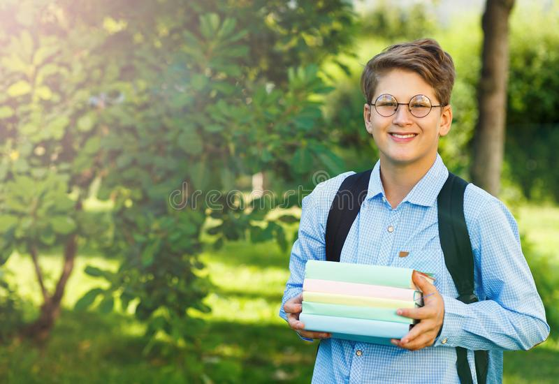 Cute, young boy in blue shirt with backpack and workbooks in his hands in front of his school. Education, Back to school. Concept royalty free stock photo