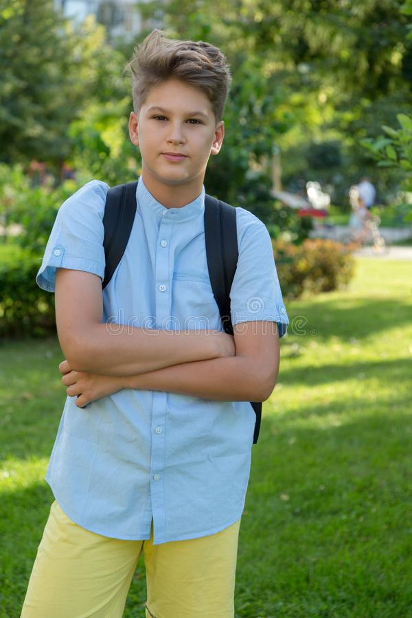 Cute, young boy in blue shirt with backpack and workbooks in his hands in front of his school. Education, Back to school. Concept royalty free stock photography