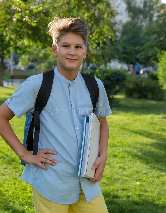 Cute, young boy in blue shirt with backpack and workbooks in his hands in front of his school. Education, Back to school. Concept royalty free stock photos