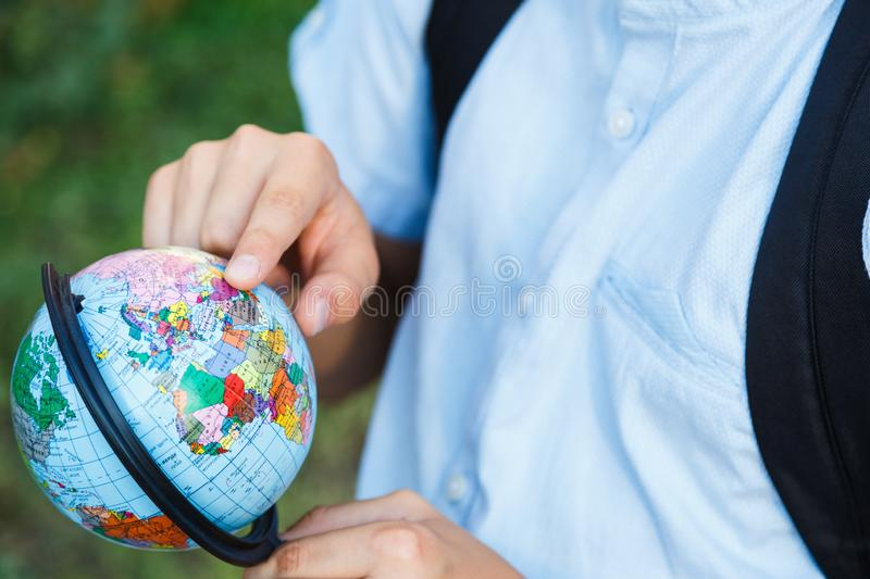 Cute, young boy in blue shirt with backpack and workbooks holds globe in his hands in front of his school. Education stock photos