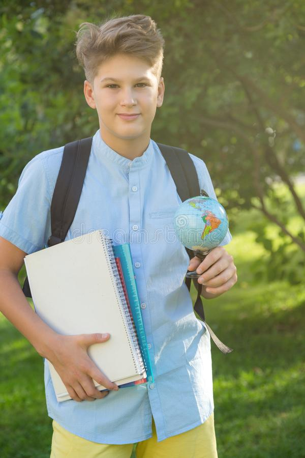 Cute, young boy in blue shirt with backpack and workbooks holds globe in his hands in front of his school. Education. Back to school concept stock images