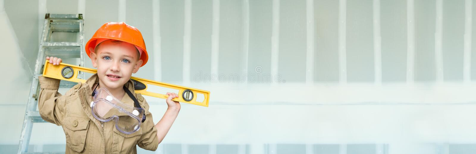 Cute Young Boy Dressed As Contractor Holding Level Against Drywall Banner Background with Ladder royalty free stock photo