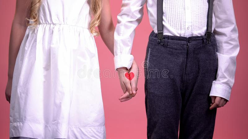 Cute young boy and girl holding hands close up, first love, Saint Valentines day stock photo