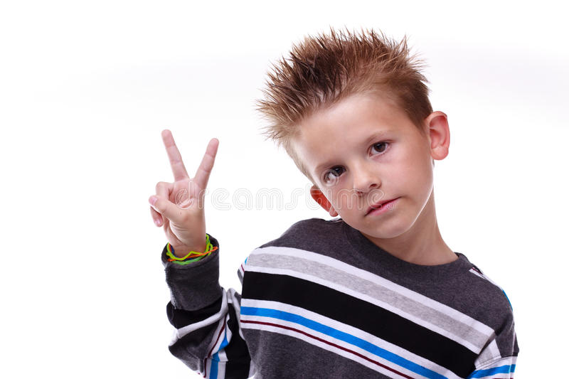 Cute young boy holding up the peace sign stock photo