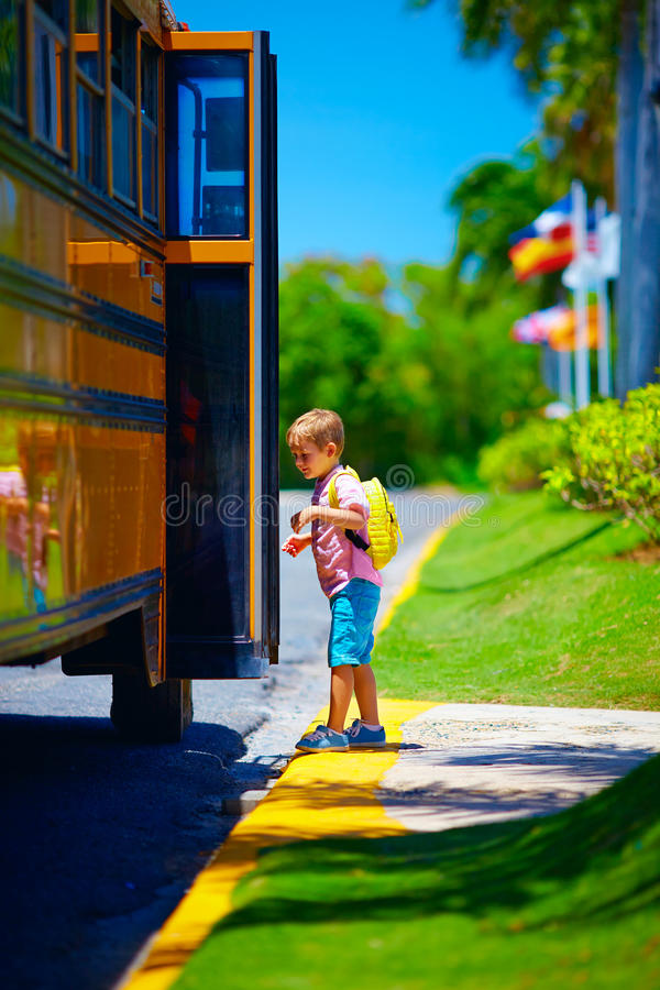 Cute young boy, kid getting on the school bus, ready to go to school. Young boy, kid getting on the school bus, ready to go to school stock photo