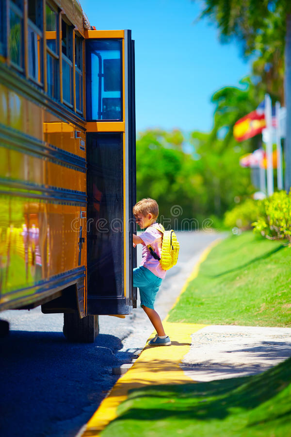 Cute young boy, kid getting on the school bus, ready to go to school. Young boy, kid getting on the school bus, ready to go to school stock photography