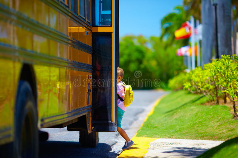 Cute young boy, kid getting on the school bus, ready to go to school. Young boy, kid getting on the schoolbus, ready to go to school royalty free stock photos