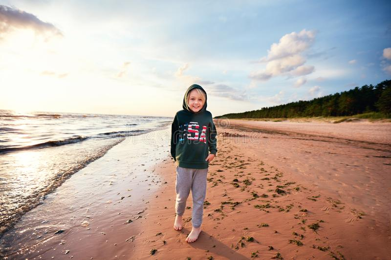 Cute young boy having fun on the sandy beach near the pine tree forest, candid lifestyle royalty free stock photo