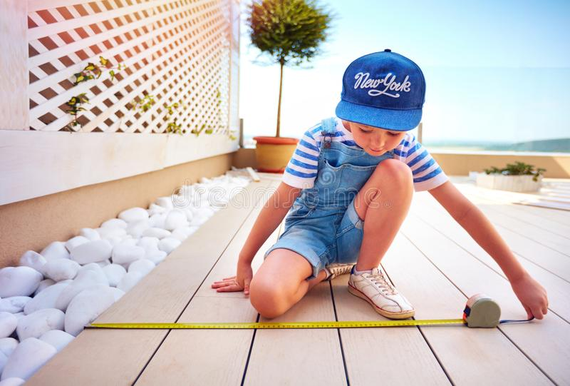Cute young boy, kid helps father with renovation of rooftop patio zone stock image