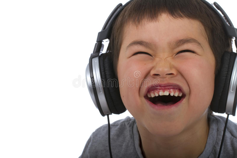 cute young boy listening to music and laughing royalty free stock photo