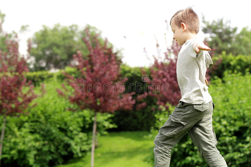 Cute young boy in the park is having fun green grass - summer time royalty free stock images