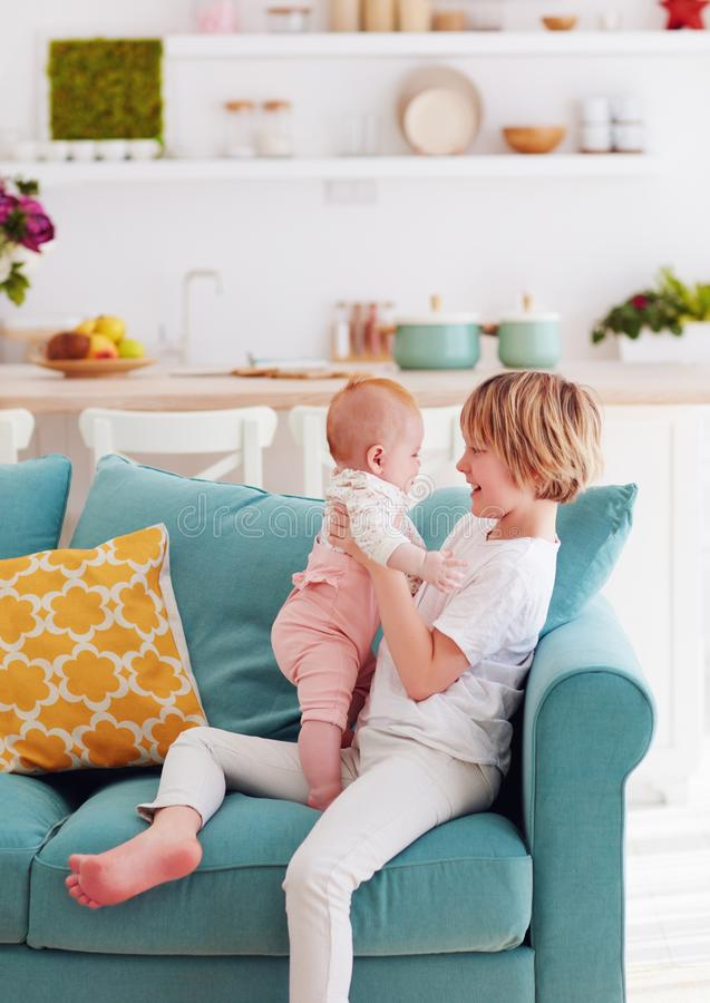 Cute young boy playing with little infant baby sister at home on the couch stock photos