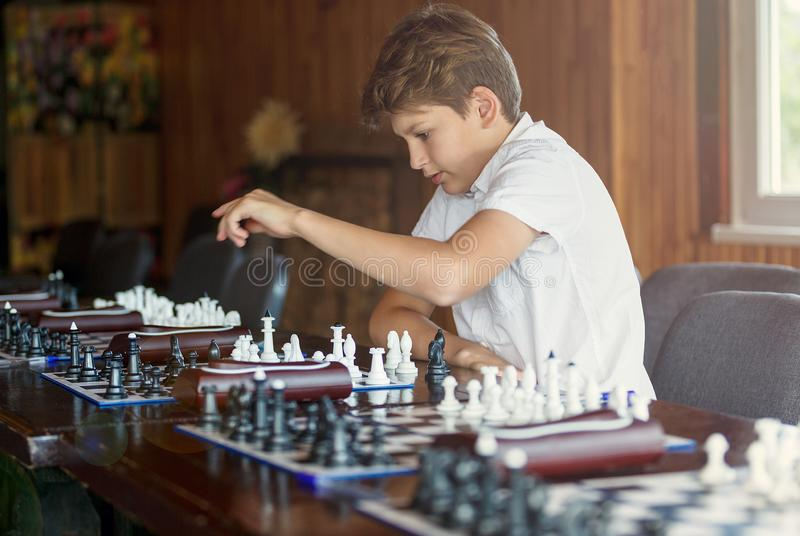 Cute, young boy plays chess with wooden chessboard. Chess tournament, lesson, camp, training stock photography