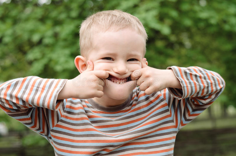 Cute young boy pulling a funny expression royalty free stock photography