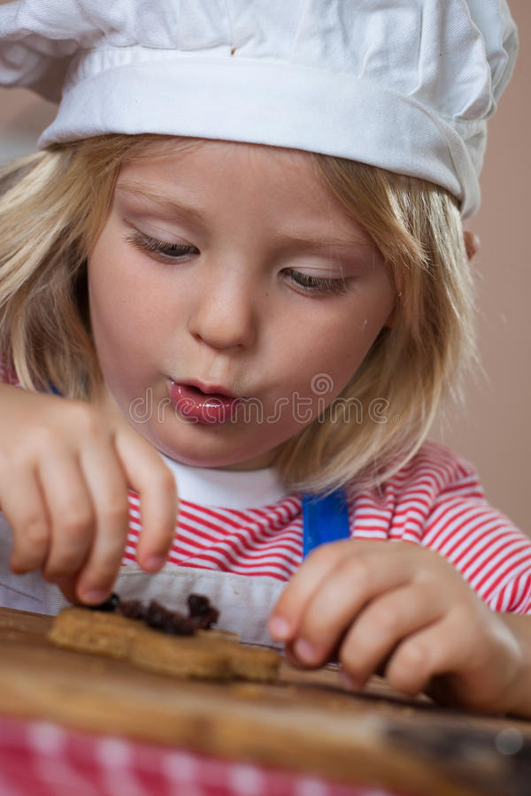 Cute young boy putting raisins on gingerbread royalty free stock photos
