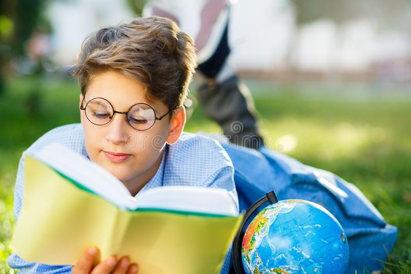 Cute, young boy in round glasses and blue shirt reads book lying on the grass in the park. Education, back to school royalty free stock photography