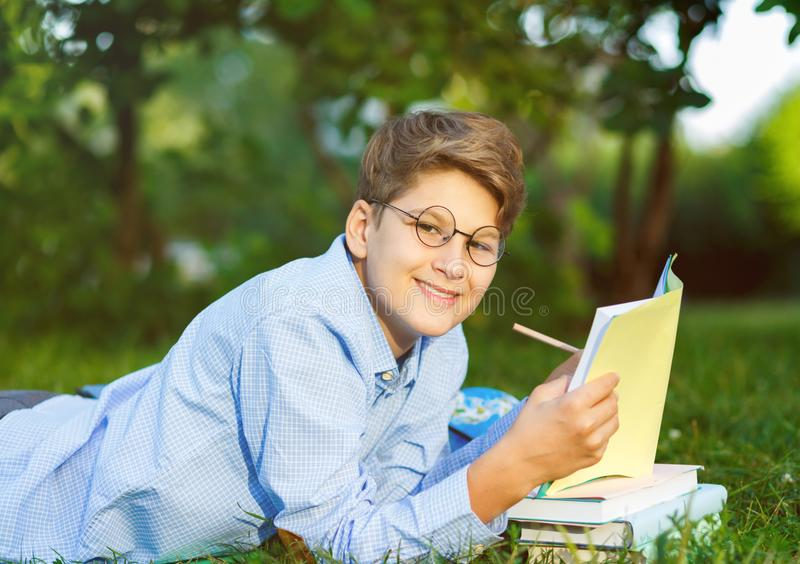 Cute, young boy in round glasses and blue shirt reads book lying on the grass in the park. Education, back to school royalty free stock photos
