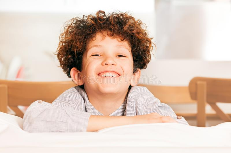 Cute young boy sitting on the couch and laughing stock photos