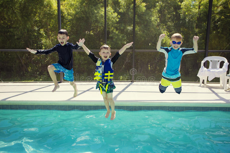 Cute young boys jumping into a swimming pool while on a fun vacation. Cute young boys jumping into an outdoor swimming pool while on a fun vacation. Fun royalty free stock photo