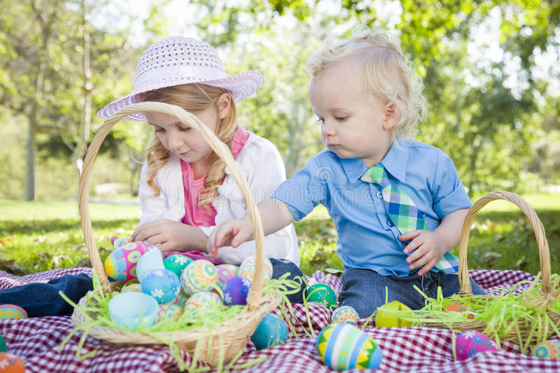 Cute Young Brother and Sister Enjoying Their Easter Eggs Outside royalty free stock images