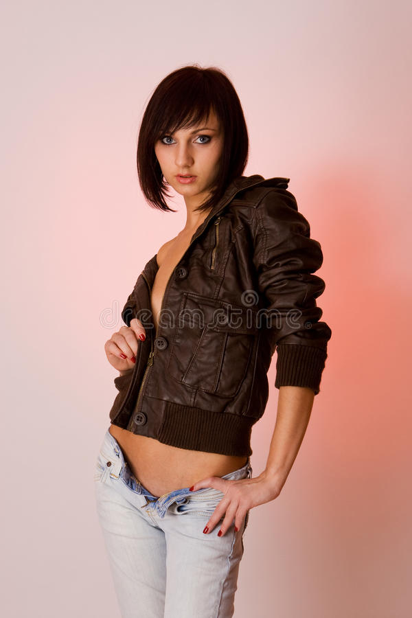 Cute young brunette girl in brown leather jacket stock photos