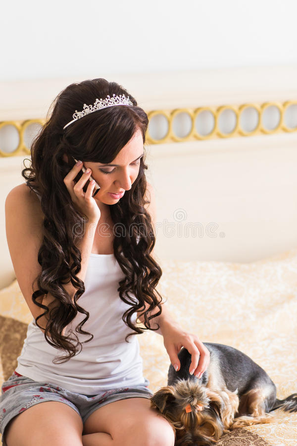 Cute young brunette girl with her Yorkshire terrier puppy sitting on a bed stock photos