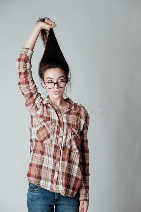 Cute young brunette girl holding her pony tail and looking surpised royalty free stock image